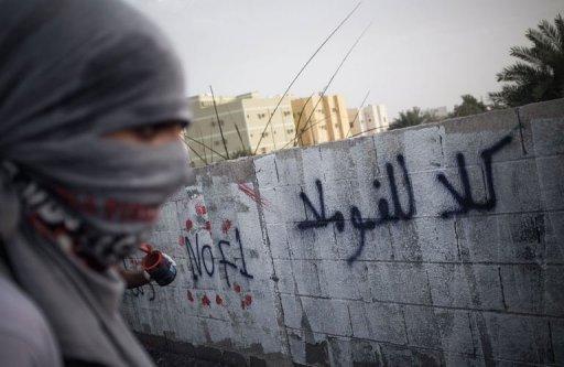 A Bahraini protester writes graffiti against the Bahrain Formula One Grand Prix in Jid Ali village, April 17, 2013. (AFP, Mohammed al-Shaikh)